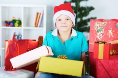 Funny boy in Santa red hat with a lot of giftboxes. Waiting for christmas Royalty Free Stock Photo