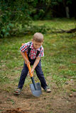 Funny boy with shovel in garden Stock Images