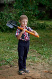 Funny boy with shovel in garden Royalty Free Stock Images