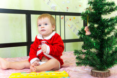 Funny boy sits near new year fir and squeezes his treasures. At home Royalty Free Stock Images