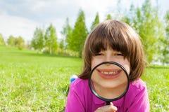 Funny boy smiles through magnifier, lays on grass Stock Photo