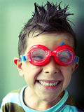 Funny boy smiling in swimming googles. Portrait view of a 5 year old boy wearing swimming goggles and making a funny face royalty free stock image