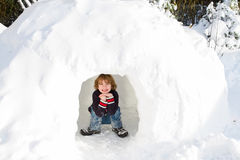Funny boy in snow igloo on a sunny winter day. Funny boy playing in a snow igloo on a sunny winter day Royalty Free Stock Image
