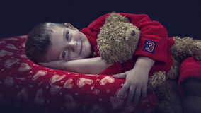 Funny boy with teddy bear on pillow before falling asleep artist. Funny boy with a teddy bear on pillow before falling asleep artistic conversion Stock Photos