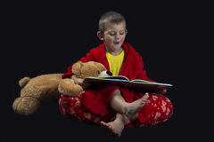 Funny boy with teddy bear reading a book before bed time Royalty Free Stock Photo