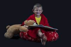 Funny boy with teddy bear reading a book before bed time Royalty Free Stock Photos