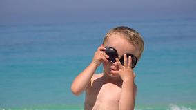 Funny boy tries to arrange sunglasses, annoyed to fail, beautiful turquoise sea. Funny boy trying to arrange sunglasses, annoyed to fail, beautiful turquoise sea stock footage