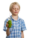 Funny boy unhappy about green smoothie Royalty Free Stock Images