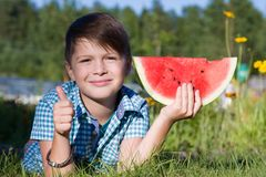 Funny boy with watermelon shows thumb up in summer park. Healthy food stock photos