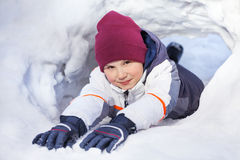 Funny boy in winter clothes playing at a snow cave Stock Image