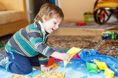Funny boy of 4 years playing with paper ships at home Stock Images