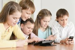 Funny boys and girls. Using digital devices together at the table at home Royalty Free Stock Images