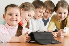 Funny boys and girls. Using digital devices together at the table at home Stock Photos