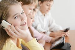Funny boys and girls. Using digital devices together at the table at home Royalty Free Stock Photo