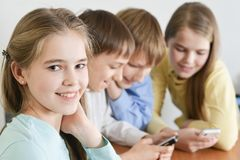 Funny boys and girls. Using digital devices together at the table at home Stock Image