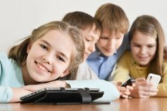 Funny boys and girls. Using digital devices together at the table at home Stock Photography