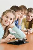 Funny boys and girls. Using digital devices together at the table at home Stock Images