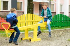Funny boys swing on a yellow swing-board stock photos