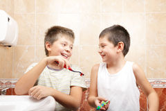 Funny boys with toothbrushes. In bathroom stock images