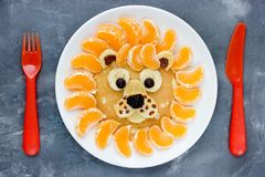 Funny breakfast idea lion pancake with tangerines stock image