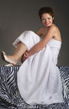Funny bride. Laughing bride in a wedding dress sits on couch Royalty Free Stock Images