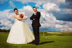 Funny bride and groom on green field Royalty Free Stock Images