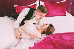 Funny bride and groom lying on bed Stock Images