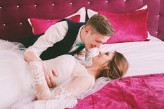 Funny bride and groom lying on crimson bed Royalty Free Stock Image