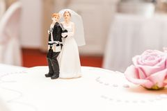 Funny bride and groom made of sugar on top of wedding cake stock photo