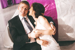 Funny bride and groom sitting near bed Stock Photos