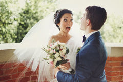 Funny bride looks shocked being hugged by a groom stock image
