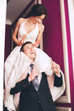 Funny bride sitting on shoulders of groom Stock Image