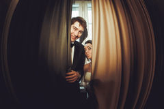 Funny bride stands behind a smiling groom hidden under the curta Stock Photography
