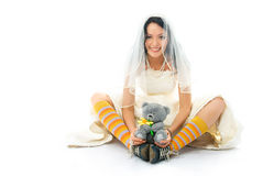 Funny bride wearing sporting shoes with a toy. Funny young brunette bride wearing old sporting shoes and colorful cocks with a toy in her hands Stock Photography