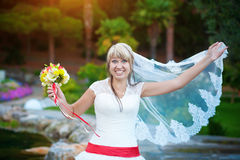 Funny bride in white dress in the park Royalty Free Stock Images