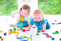 Funny brother and sister playing with colorful blocks Royalty Free Stock Photos
