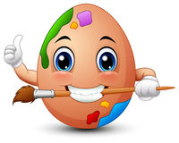 Funny brown easter egg painter gives a thumbs up while biting a brush Stock Photos
