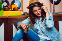 Funny brunette firl laughs near bar table with glass of cocktail Stock Photo