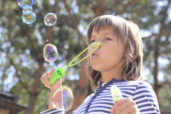Funny bubbles. Boy inflates bubbles outdoor at summer Stock Images
