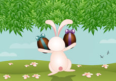 Funny bunny with chocolate eggs Royalty Free Stock Photos