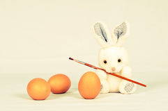Funny bunny with eggs and brush Stock Images