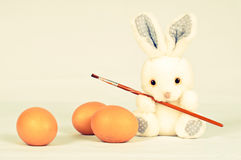 Funny bunny with eggs and brush Royalty Free Stock Photography