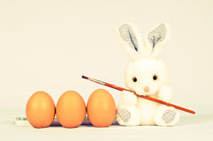 Funny bunny with eggs and brush Royalty Free Stock Photos