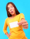 Funny business card. Surprised woman shocked showing a card with copy space, on a colorful background Stock Image