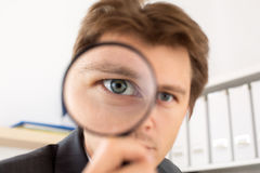 Funny business man holding magnifying glass. Portrait. Private detective investigation, layer, crime, business research or security concept Stock Photos