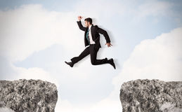 Funny business man jumping over rocks with gap Stock Photo