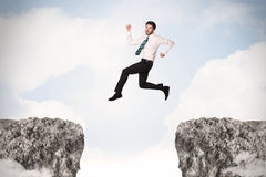 Funny business man jumping over rocks with gap Royalty Free Stock Photography