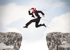 Funny business man jumping over rocks with gap Royalty Free Stock Photos