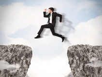 Funny business man jumping over rocks with gap. Concept Royalty Free Stock Image