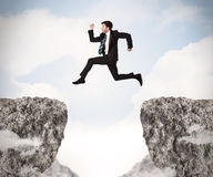 Funny business man jumping over rocks with gap Stock Image